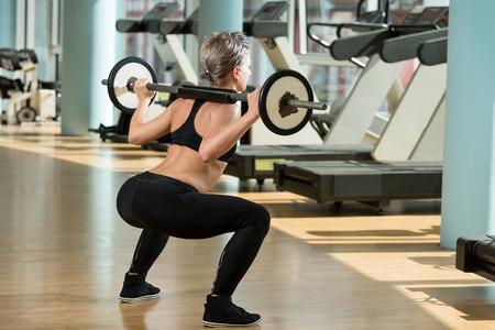 levantamiento de pesas: Mujer hermosa en forma haciendo sentadillas con barra En El Gimnasio