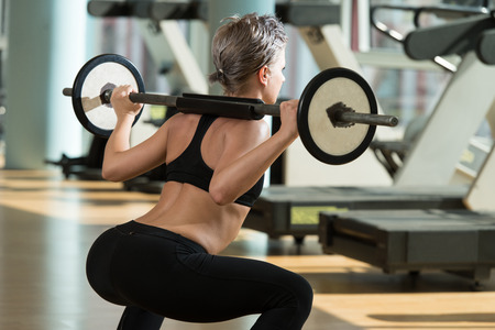 Beautiful Fit Woman Doing Barbell Squats In The Gym Standard-Bild