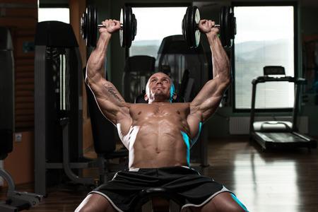 Stattlicher junger Mann tun Hantel Schrägbankdrücken training In Der Gymnastik Standard-Bild