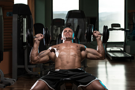 incline: Handsome Young Man Doing Dumbbell Incline Bench Press Workout In Gym