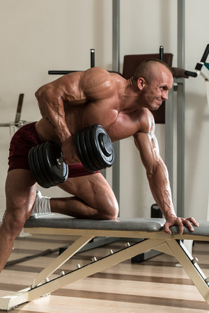body conscious: Healthy Man Doing Back Exercises In The Gym With Dumbbell