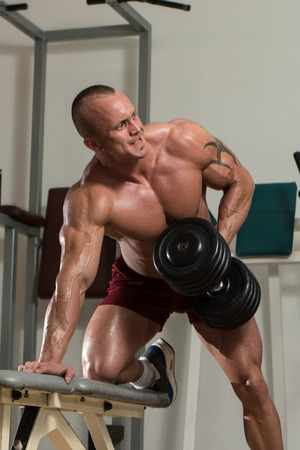 Healthy Man Doing Back Exercises In The Gym With Dumbbell photo