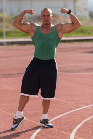Bodybuilder Performing Front Double Biceps Poses At Tennis Place photo