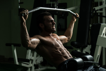 muscular body: Young Man Doing Heavy Weight Exercise For Back