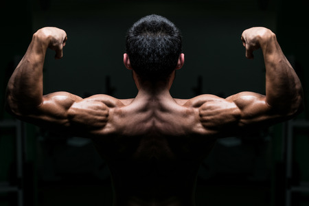 Young Male Athlete Flexing Back Muscles photo