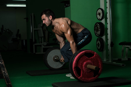 Muscular Man Lifting Dead Lift In The Gym photo