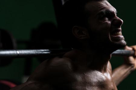 muscle training: Junger Mann, der Langhantel Kniebeugen - Einer der besten Body Building-�bung f�r Beine Lizenzfreie Bilder