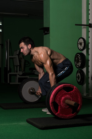 Muscular Man Lifting Dead Lift In The Gym