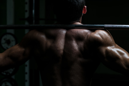boy body: Young Man Performing Barbell Squats - One Of The Best Body Building Exercise For Legs