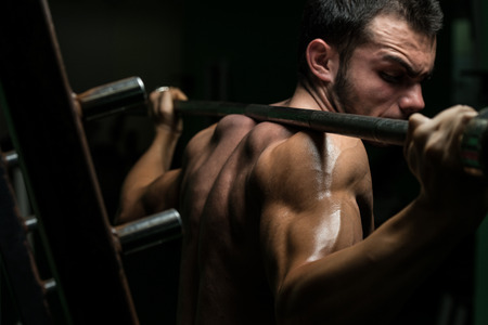 Junger Mann, der Langhantel Kniebeugen - Einer der besten Body Building-Übung für Beine Standard-Bild