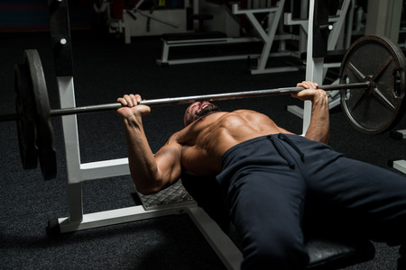 body conscious: Mature Man In Gym Exercising On The Bench Press Stock Photo