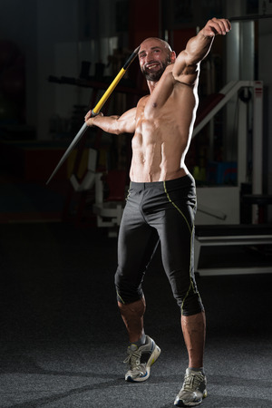 Mature Man Athlete Practicing To Throw A Javelin photo