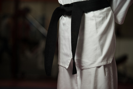 martial arts: Man In A White Kimono And Belt For Martial Arts