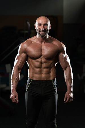 Portrait Of A Physically Fit Mature Man In A Healthy Club With Dramatic Lighting Stock Photo