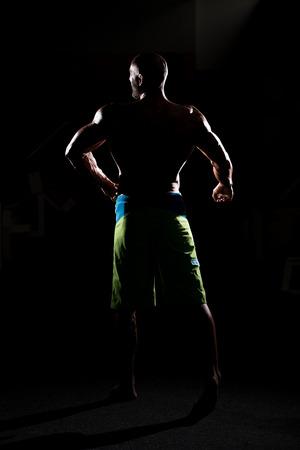 siluet: Siluet Muscular Man Flexing Muscles Stock Photo