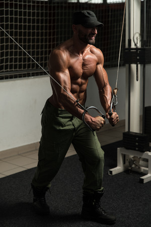 crossover: Mature Bodybuilder Is Working On His Chest With Cable Crossover In A Dark Gym Stock Photo