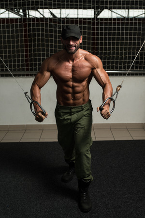 Mature Bodybuilder Is Working On His Chest With Cable Crossover In A Dark Gym Stock Photo