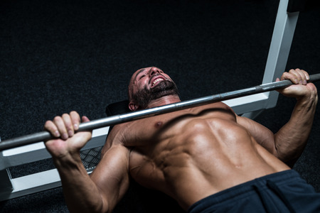 body building: Mature Man In Gym Exercising On The Bench Press Stock Photo