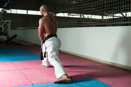 limbering: Male Martial Arts Instructor Preparing For Class - Warming Up and Stretching