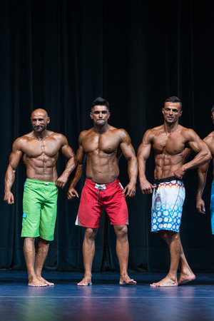 physique: Mens Physique Posing During A Bodybuilding Competition