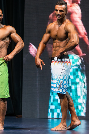Mens Physique Posing During A Bodybuilding Competition