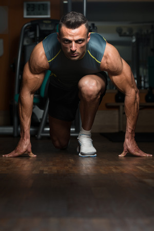 body line: Strong Muscular Men Kneeling On The Floor - Almost Like Sprinter Starting Position Stock Photo