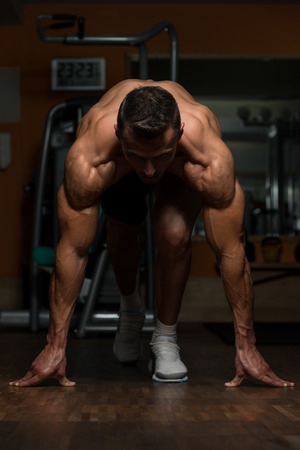well build: Strong Muscular Men Kneeling On The Floor - Almost Like Sprinter Starting Position Stock Photo