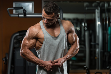 muscle building: Portrait Of A Physically Fit Young Man - Flexing Muscles