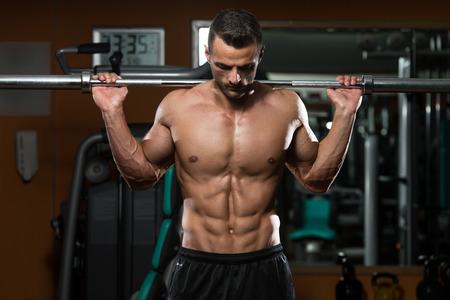Junger Mann, der Kniebeugen - eine der besten Bodybuilding Übung für die Beine