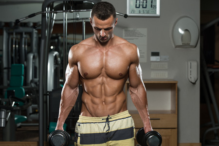 body torso: Young Man Working Out Biceps - Dumbbell Concentration Curls Stock Photo