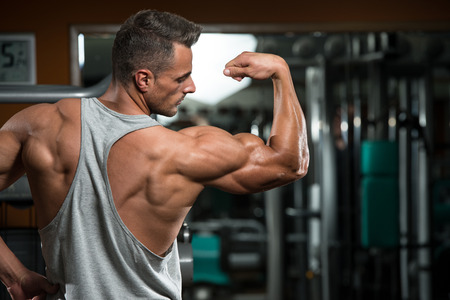 muscle: Portrait Of A Physically Fit Young Man - Flexing Muscles