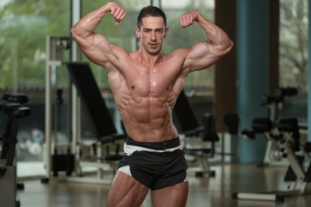 men standing: Serious Men Standing In The Gym And Flexing Muscles