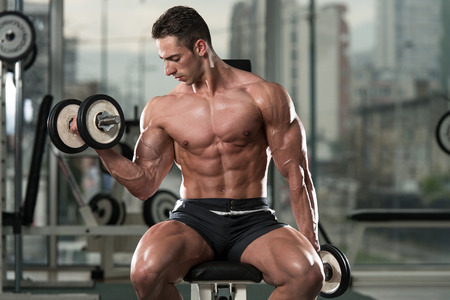 Young Man Working Out Biceps - Dumbbell Concentration Curls Stock Photo