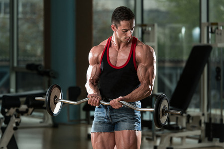 body conscious: Muscular Man Doing Heavy Weight Exercise For Biceps