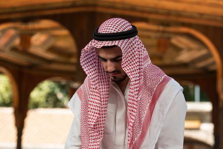 islamic pray: Young Muslim Man Making Traditional Prayer To God While Wearing A Traditional Cap Dishdasha Stock Photo