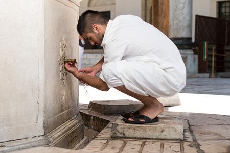 islamic prayer: Muslim Man Preparing To Take Ablution In Mosque Stock Photo