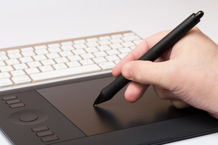 Closeup Of One Hand Drawing On A Computer Graphics Tablet photo