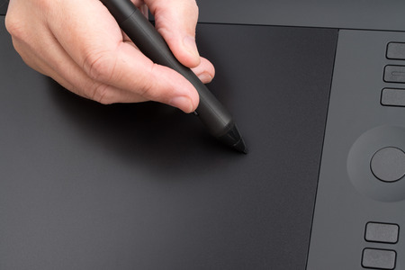graphics tablet: Closeup Of One Hand Drawing On A Computer Graphics Tablet Stock Photo
