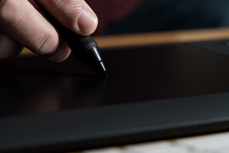 wacom: Closeup Of One Hand Drawing On A Computer Graphics Tablet Stock Photo