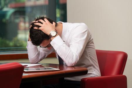 Junger Geschäftsmann mit Problemen und Stress im Büro Standard-Bild