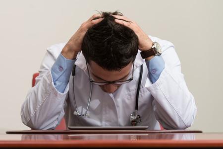 Betonte heraus Doktor mit den Händen sitzen am Tisch im Konferenzraum Standard-Bild