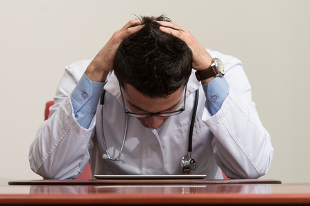 Stressed Out Doctor With Hands Clasped Sitting At Table In Conference Room photo