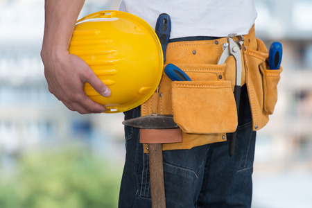 construction equipment: Close-Up Of Hard Hat Holding By Construction Worker