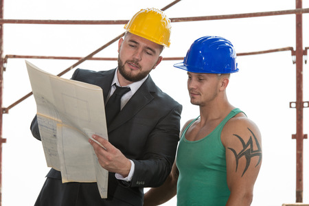 Group Of Male Architect And Construction Worker On Construction Site photo