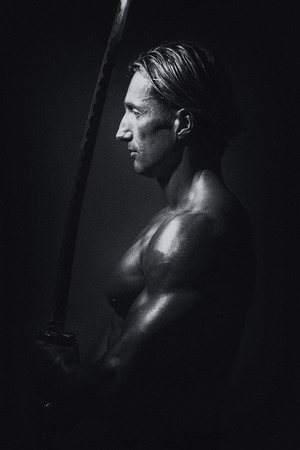 Portrait Of A Handsome Muscular Ancient Warrior With A Sword photo
