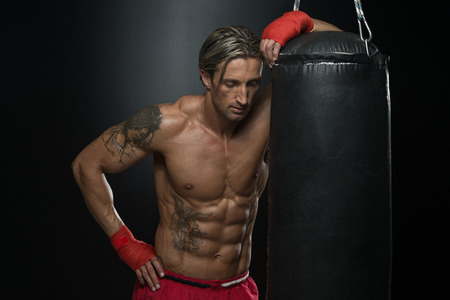 sports backgrounds: A Man With A Tattoo In Red Boxing Gloves - Boxing On Black Background - The Concept Of A Healthy Lifestyle - The Idea For The Film About Boxing