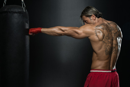 A Man With A Tattoo In Red Boxing Gloves - Boxing On Black Background - The Concept Of A Healthy Lifestyle - The Idea For The Film About Boxing photo