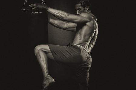 boxeador: Un hombre con un tatuaje en los guantes de boxeo rojos - Boxeo En Fondo Negro - El concepto de un estilo de vida saludable - La idea de la película sobre el boxeo