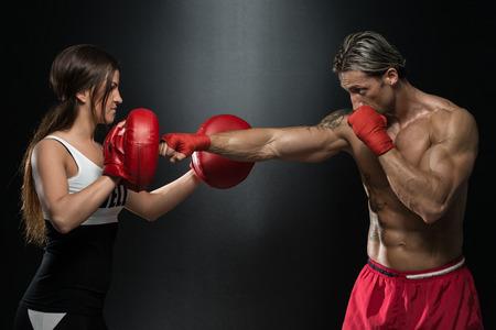 guantes de boxeo: Culturismo pareja posando con guantes de boxeo en Negro Foto de archivo