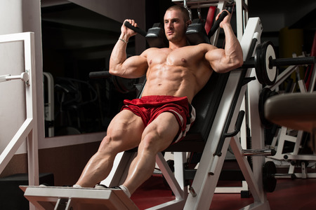 muscle building: Male Bodybuilder Doing Heavy Weight Exercise For Legs